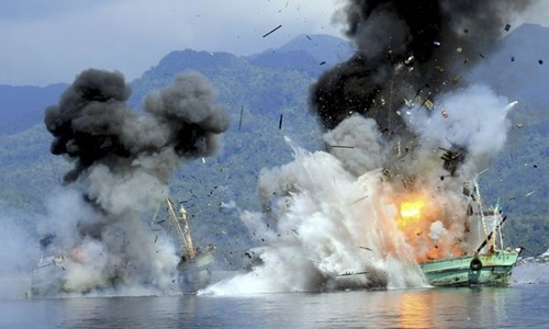 Two foreign flagged fishing boats registered in Papua New Guinea are destroyed by the Indonesian Navy after they were seized earlier for supposedly illegal fishing off the coast of Ambon, Maluku December 21, 2014 in this photo taken by Antara Foto.  REUTERS/Antara Foto/Izaac Mulyawan (INDONESIA - Tags: POLITICS MARITIME TPX IMAGES OF THE DAY TRANSPORT)   ATTENTION EDITORS - THIS PICTURE WAS PROVIDED BY A THIRD PARTY. FOR EDITORIAL USE ONLY. NOT FOR SALE FOR MARKETING OR ADVERTISING CAMPAIGNS. THIS PICTURE IS DISTRIBUTED EXACTLY AS RECEIVED BY REUTERS, AS A SERVICE TO CLIENTS.  MANDATORY CREDIT. INDONESIA OUT. NO COMMERCIAL OR EDITORIAL SALES IN INDONESIA